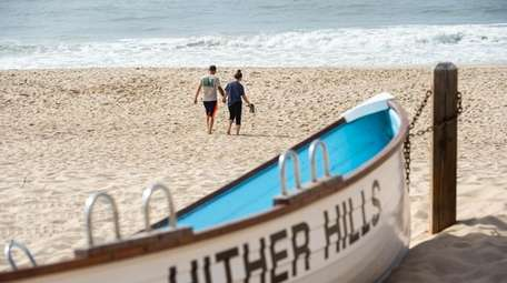 A couple walks on the beach at Hither