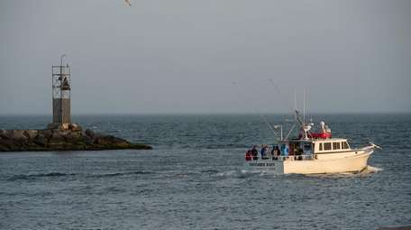 A charter fishing boat exits Montauk Harbor in