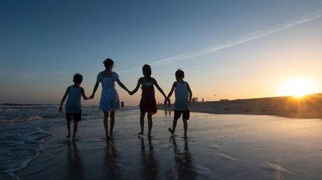 A family walks on Robert Moses Beach Monday