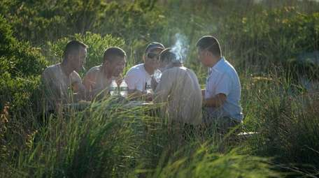 Men play cards in Captree State Park on