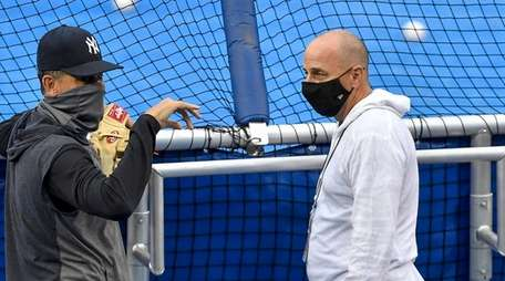 Yankees manager Aaron Boone, left, talks with general