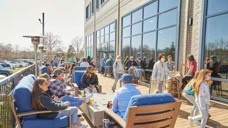 Patrons enjoy outdoor dining at Peconic County Brewing