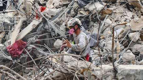 A search-and-rescue team member moves through the debris