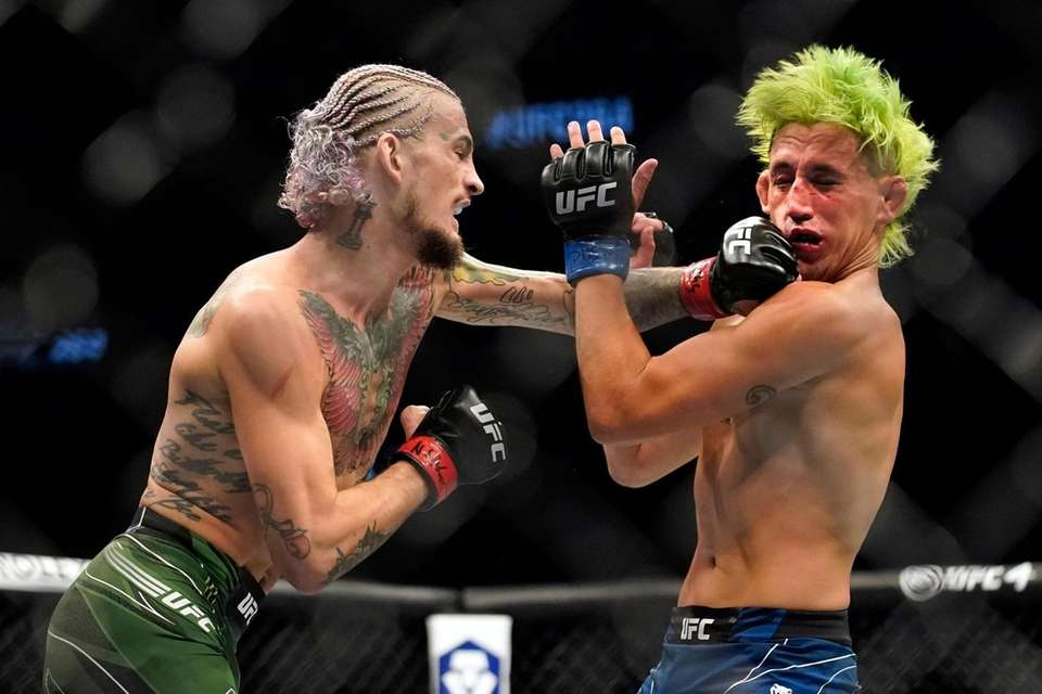Sean O'Malley, left, punches Kris Moutinho in a