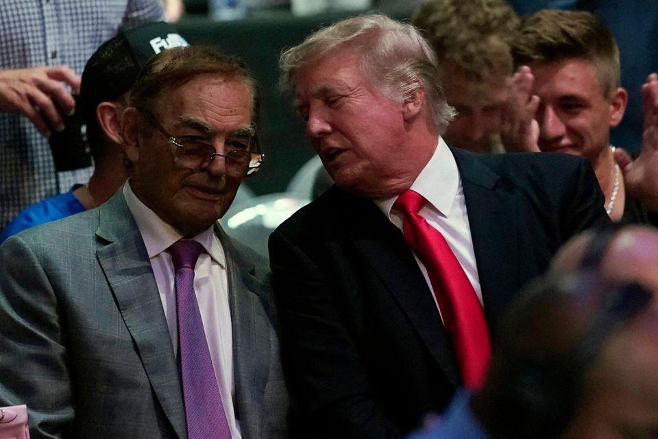 Former U.S. President Donald Trump, right, attends UFC