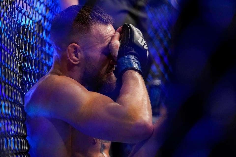 Conor McGregor sits on the mat after an