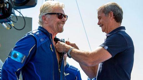 Virgin Galactic founder Richard Branson, left, receives a