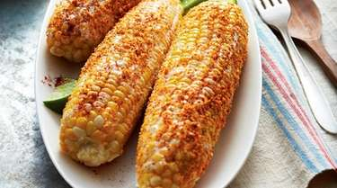 Corn on the cob is brushed with mayonnaise