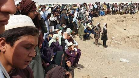Stranded people gather Thursday in Chaman, Pakistan, near