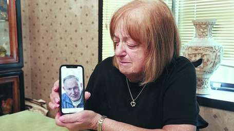 Carol Riggs holds a cellphone with a photo