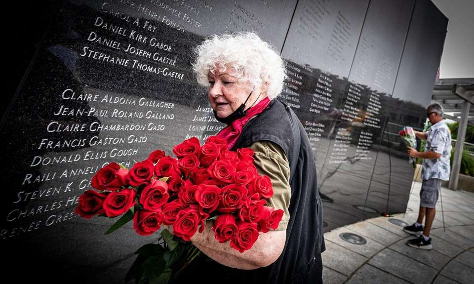Sayville resident Fran Haas carries roses Saturday to