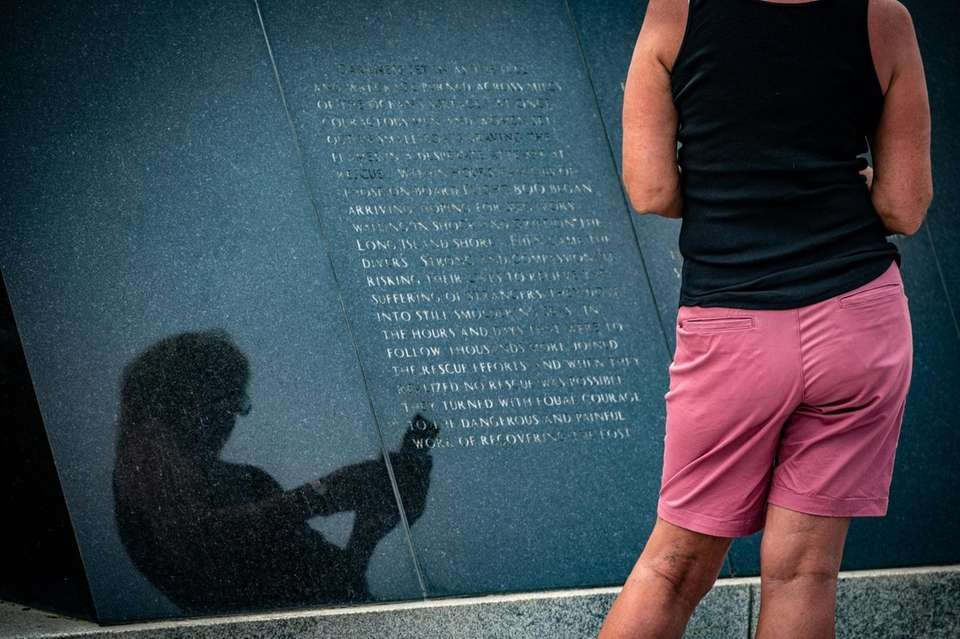 A visitor to the Mastic Beach memorial for