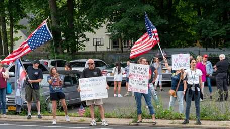 Protesters gather outside the Stony Brook LIRR station.