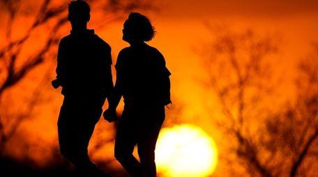 A couple walks through a park at sunset