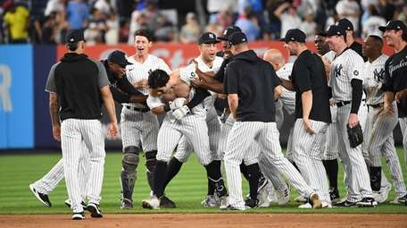 The Yankees' Ryan LaMarre is mobbed by teammates