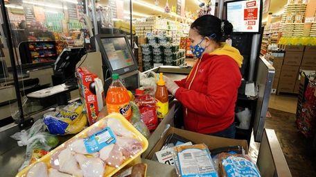 Cashier Reena Hurtado of Freeport checks out a