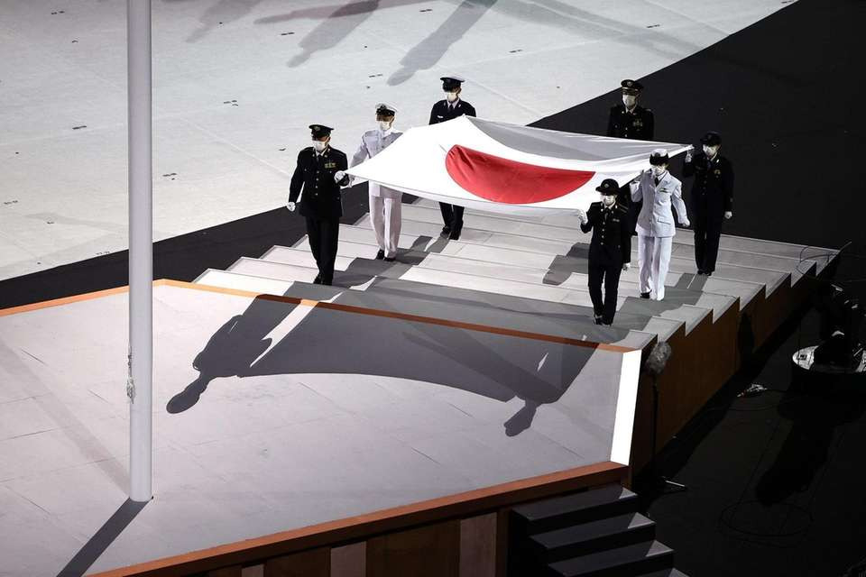 The Japanese flag is carried onto the stage