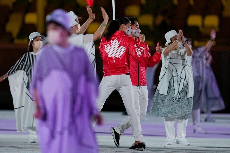 Miranda Ayim and Nathan Hirayama, of Canada, carry