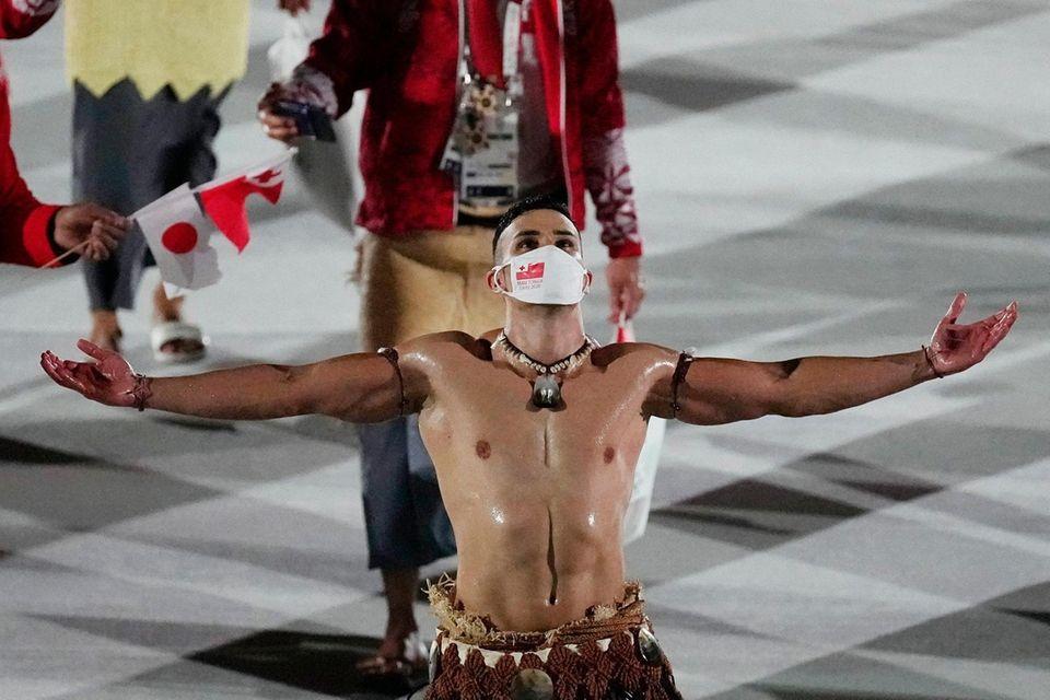 Pita Taufatofua, of Tonga, walks during the opening