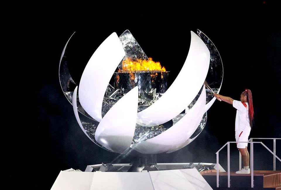 Naomi Osaka of Team Japan lights the Olympic
