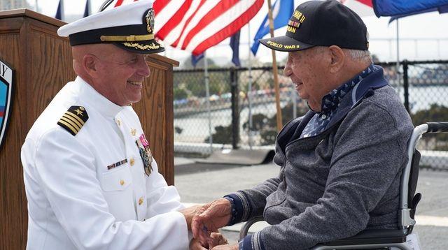 Retired Capt. Steve Gilmore greets William Gómez, right,