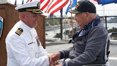 Retired Capt. Steve Gilmore greets William Gomez, right,