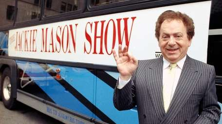 Actor/comedian Jackie Mason stands beside a bus displaying