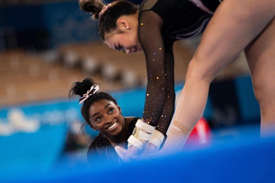 US gymnast Simone Biles (L) speaks to a