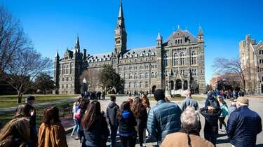 Prospective students and their parents approach tour Georgetown
