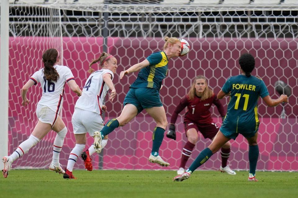 Australia's Clare Polkinghorne, center, heads the ball during
