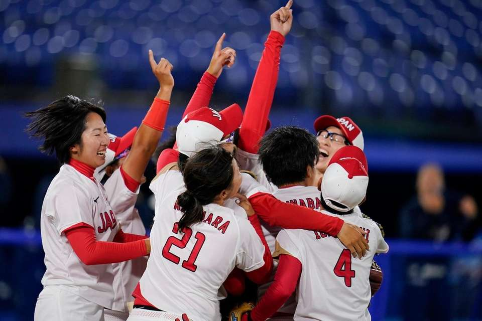 Members of team Japan celebrate after a softball