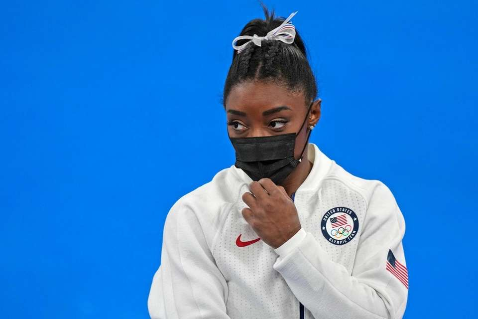 Simone Biles, of the United States, stands wearing