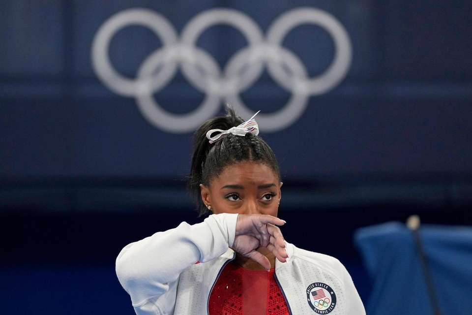 Simone Biles, of the United States, watches gymnasts