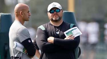 Jets general manager Joe Douglas, right, talks with