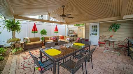 The backyard pergola over brick and cement patio.