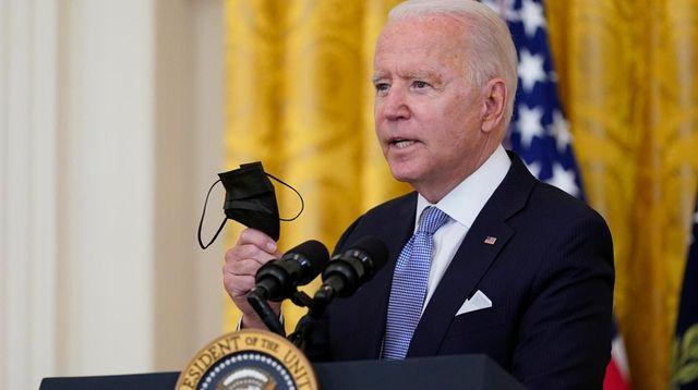 President Joe Biden holds a face mask as