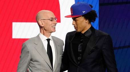 NBA Commissioner Adam Silver greets Cade Cunningham, who