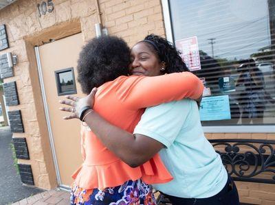 Shirley Cobb and Adesuwa Obasohan Watson hug outside