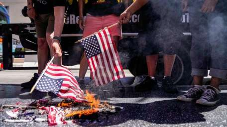 Protesters set an American flag on fire near
