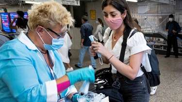 Long Island Rail Road employees hand out masks