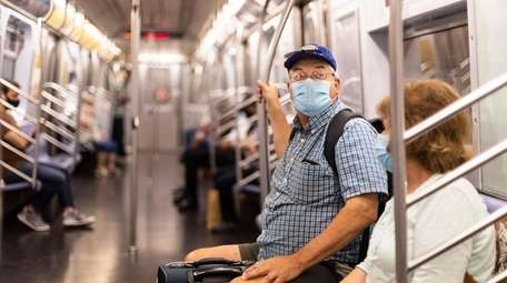 People wear masks on a subway train in