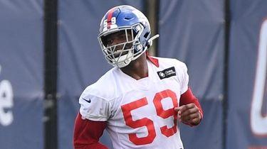 Giants linebacker Lorenzo Carter looks on from the