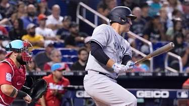 Yankees' Anthony Rizzo, right, watches after hitting a