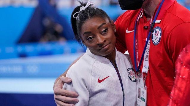 Coach Laurent Landi embraces Simone Biles, after she