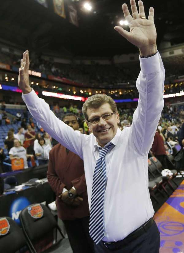 Connecticut head coach Geno Auriemma waves to fans