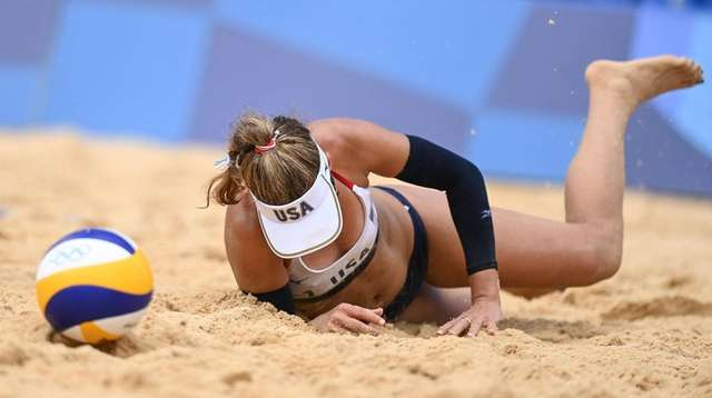 USA's April Ross falls in the sand in