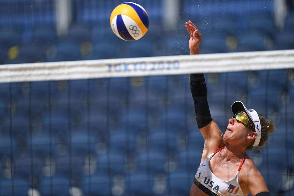 USA's April Ross spikes the ball in their