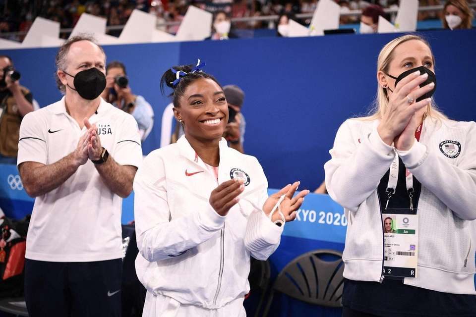 USA's Simone Biles (C) reacts next to her
