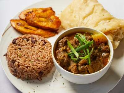 Curry goat with roti, fried plantains, rice and