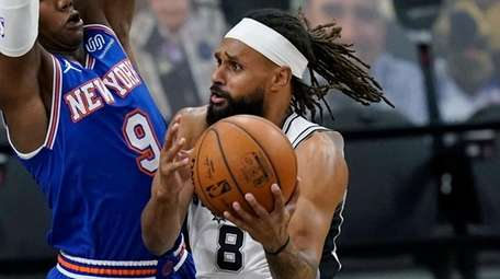 Spurs guard Patty Mills drives to the basket